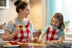 Happy family in the kitchen. Happy loving family are preparing bakery together. Mother and child daughter girl are cooking cookies and having fun in the kitchen stock photography
