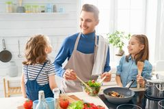 Happy family in the kitchen. Healthy food at home. Happy family in the kitchen. Father and children daughters are preparing proper meal stock photography