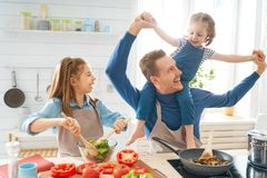 Happy family in the kitchen. Healthy food at home. Happy family in the kitchen. Father and children daughters are preparing proper meal royalty free stock photography