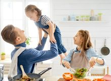 Happy family in the kitchen. Healthy food at home. Happy family in the kitchen. Father and children daughters are preparing proper meal stock images