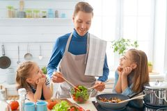 Happy family in the kitchen. Healthy food at home. Happy family in the kitchen. Father and children daughters are preparing proper meal royalty free stock images