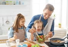 Happy family in the kitchen. Healthy food at home. Happy family in the kitchen. Father and children daughters are preparing proper meal stock image