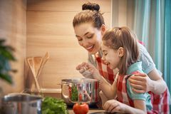 Happy family in the kitchen. Healthy food at home. Happy family in the kitchen. Mother and child daughter are preparing on the cooker royalty free stock photos