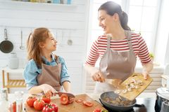 Happy family in the kitchen. Healthy food at home. Happy family in the kitchen. Mother and child daughter are preparing proper meal royalty free stock photo