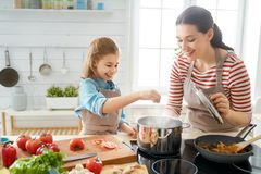 Happy family in the kitchen. Healthy food at home. Happy family in the kitchen. Mother and child daughter are preparing proper meal stock photography