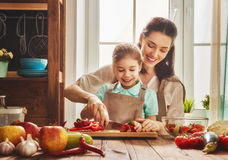 Happy family in the kitchen. Healthy food at home. Happy family in the kitchen. Mother and child daughter are preparing the vegetables and fruit royalty free stock photography