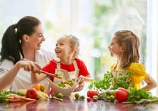 Happy family in the kitchen. Healthy food at home. Happy family in the kitchen. Mother and children daughters are preparing the vegetables stock photos