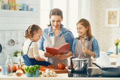 Happy family in the kitchen. Healthy food at home. Happy family in the kitchen. Mother and children daughters are preparing vegetables stock photography