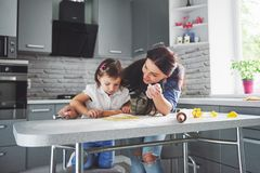 Happy family in the kitchen. Holiday food concept. Mother and daughter preparing the dough, bake cookies. Happy family. In making cookies at home. Homemade food royalty free stock photography