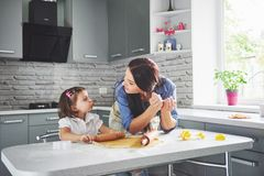 Happy family in the kitchen. Holiday food concept. Mother and daughter preparing the dough, bake cookies. Happy family. In making cookies at home. Homemade food royalty free stock photo