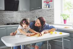 Happy family in the kitchen. Holiday food concept. Mother and daughter preparing the dough, bake cookies. Happy family. In making cookies at home. Homemade food royalty free stock images
