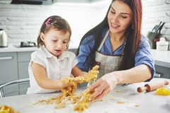 Happy family in the kitchen. Holiday food concept. Mother and daughter preparing the dough, bake cookies. Happy family. In making cookies at home. Homemade food stock photos