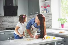 Happy family in the kitchen. Holiday food concept. Mother and daughter preparing the dough, bake cookies. Happy family. In making cookies at home. Homemade food stock photo