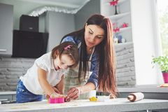 Happy family in the kitchen. Holiday food concept. Mother and daughter preparing the dough, bake cookies. Happy family. In making cookies at home. Homemade food stock image
