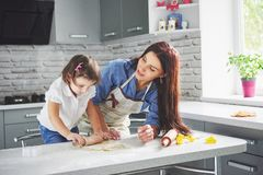 Happy family in the kitchen. Holiday food concept. Mother and daughter preparing the dough, bake cookies. Happy family. In making cookies at home. Homemade food royalty free stock image