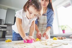 Happy family in the kitchen. Holiday food concept. Mother and daughter preparing the dough, bake cookies. Happy family. In making cookies at home. Homemade food stock images