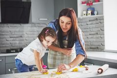 Happy family in the kitchen. Holiday food concept. Mother and daughter preparing the dough, bake cookies. Happy family. In making cookies at home. Homemade food royalty free stock photos