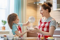 Happy family in the kitchen. Happy loving family are preparing bakery together. Mother and child daughter girl are cooking cookies and having fun in the kitchen stock image