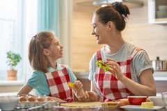 Happy family in the kitchen. Happy loving family are preparing bakery together. Mother and child daughter girl are cooking cookies and having fun in the kitchen stock photo