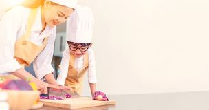 Happy family in the kitchen. Mom teaching son for cook healthy food. In summer holiday stock image