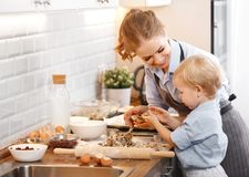 Happy family in kitchen. mother and child baking cookies. Happy family in kitchen. mother and child son baking cookies together Royalty Free Stock Photos