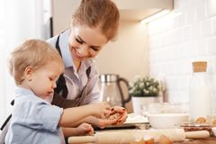 Happy family in kitchen. mother and child baking cookies. Happy family in kitchen. mother and child son baking cookies together Stock Images