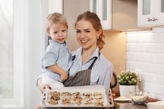 Happy family in kitchen. mother and child baking cookies. Happy family in kitchen. mother and child son baking cookies together Royalty Free Stock Images