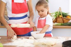 Happy family in the kitchen. Mother and child daughter cooking holiday pie or cookies for Mothers day. Casual lifestyle photo series in real life interior Royalty Free Stock Images