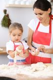 Happy family in the kitchen. Mother and child daughter cooking holiday pie or cookies for Mothers day. Casual lifestyle photo series in real life interior Stock Photo
