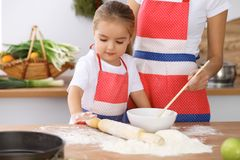 Happy family in the kitchen. Mother and child daughter cooking holiday pie or cookies for Mothers day. Casual lifestyle photo series in real life interior Royalty Free Stock Image