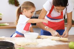 Happy family in the kitchen. Mother and child daughter cooking holiday pie or cookies for Mothers day. Casual lifestyle photo series in real life interior Royalty Free Stock Photo