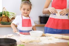Happy family in the kitchen. Mother and child daughter cooking holiday pie or cookies for Mothers day. Casual lifestyle photo series in real life interior Royalty Free Stock Photos