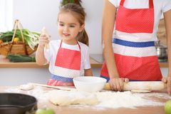 Happy family in the kitchen. Mother and child daughter cooking holiday pie or cookies for Mothers day Royalty Free Stock Photo