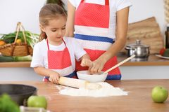 Happy family in the kitchen. Mother and child daughter cooking holiday pie or cookies for Mothers day. Casual lifestyle photo series in real life interior Stock Photos