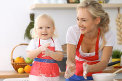 Happy family in the kitchen. Mother and child daughter cooking holiday pie or cookies for Mothers day Stock Images