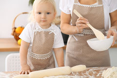 Happy family in the kitchen. Mother and child daughter cooking holiday pie or cookies for Mothers day Royalty Free Stock Image