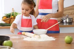 Happy family in the kitchen. Mother and child daughter cooking holiday pie or cookies for Mothers day. Casual lifestyle photo series in real life interior Royalty Free Stock Photography
