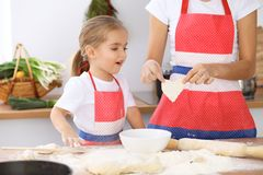 Happy family in the kitchen. Mother and child daughter cooking holiday pie or cookies for Mothers day Royalty Free Stock Photos