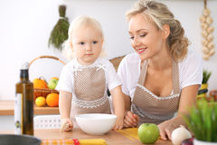 Happy family in the kitchen. Mother and child daughter cooking tasty breakfest Stock Images