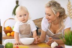 Happy family in the kitchen. Mother and child daughter cooking tasty breakfest Stock Photo