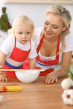 Happy family in the kitchen. Mother and child daughter cooking tasty breakfest Royalty Free Stock Images
