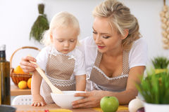 Happy family in the kitchen. Mother and child daughter cooking tasty breakfest. Happy family in the kitchen. Mother and child daughter  cooking tasty breakfest Royalty Free Stock Photo