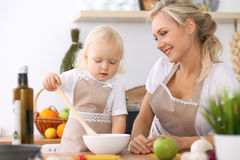 Happy family in the kitchen. Mother and child daughter cooking tasty breakfest. Happy family in the kitchen. Mother and child daughter  cooking tasty breakfest Royalty Free Stock Photos