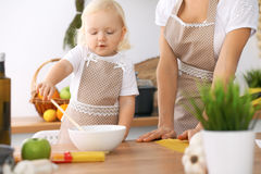 Happy family in the kitchen. Mother and child daughter cooking tasty breakfest. Happy family in the kitchen. Mother and child daughter  cooking tasty breakfest Royalty Free Stock Images