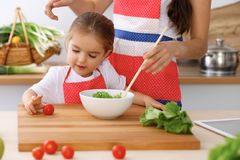 Happy family in the kitchen. Mother and child daughter  cooking tasty breakfest of fresh salad. Little helper slicing an Royalty Free Stock Photo