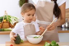 Happy family in the kitchen. Mother and child daughter cooking tasty breakfest of fresh salad. Little helper slicing an. Happy family in the kitchen. Mother and Stock Images