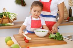 Happy family in the kitchen. Mother and child daughter cooking tasty breakfest of fresh salad. Little helper slicing an. Happy family in the kitchen. Mother and Royalty Free Stock Image