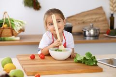 Happy family in the kitchen. Mother and child daughter  cooking tasty breakfest of fresh salad. Little helper slicing an. Happy family in the kitchen. Mother and Stock Photos