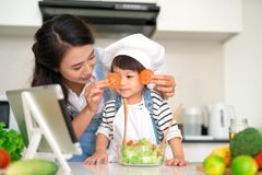 Happy family in the kitchen. Mother and child daughter are preparing the vegetables and fruit royalty free stock images
