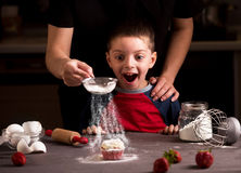 Happy family in the kitchen. Mother and child preparing cookies in kitchen. Mother pouring sugar powder like a snow royalty free stock photos